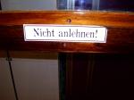 Nicht anlehnen-Schild an der Tür (von innen)
