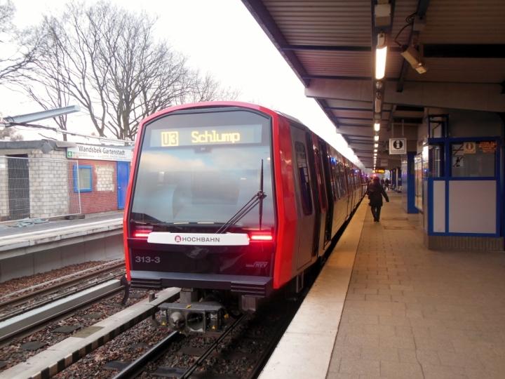 Am 20. Dezember musste ich noch ein zweites Mal hinsehen: DT5 313 fuhr zusammen mit Nr. 310 den zweiten Umlauf. Was daran verwunderlich ist? Niemand hat die Anlieferung des Zuges am 16.12. mitbekommen. Wenn ein neuer Zug plötzlich in Ohlsdorf steht ist das etwas aufmerksamkeitserregend. Schon nach vier Tagen ging er in den Fahrgastbetrieb, das Foto zeigt den Zug 310/313 kurz vor seiner Abfahrt in Wandsbek-Gartenstadt an seinem ersten Betriebstag.