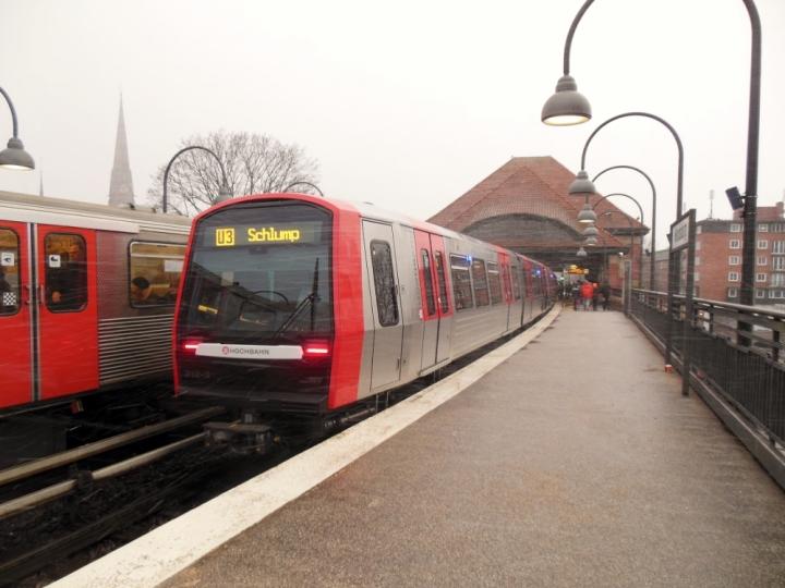 """Pünktlich zum Nikolaus wurde Hamburg erstmals in diesem Winter in Schnee gehüllt. Und wie heißt es so schön: """"Unverhofft kommt oft"""" – Gemäß dem Sprichwort kam gerade im Moment des Fotos ein schöner Schneesturm an der Mundsburg vorbeigezogen. Der Zug 310/312 wird gleich die Haltestelle Mundsburg verlassen, der benachbarte DT3 blieb unbekannt."""
