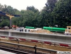 """Weitere grüne Rohre. Hinten sieht man, dass die Bahnsteigkanten mittels Dachpappe """"zusammengefügt"""" werden. Vorne: In regelmäßigen Abständen sind noch solche weißen Styroporstücke(???) zwischen den Elementen."""