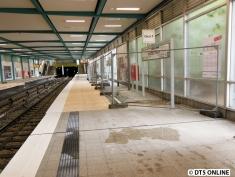 Der Bahnsteig ist mit Holzplatten teilerhöht, die Bodenfliesen werden bei den Durchfahrten verlegt. Hinter dem Bauzaun sieht man den Boden.