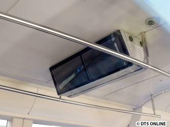 oben zwei Bildschirme für das Fahrgastfernsehen zwischen den Haltestangen