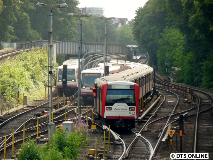 """DT4 141 war auf der Leinpfadbrücke hinter Sierichstraße zum Stehen gekommen, alle Fahrgäste mussten evakuiert werden (nach vierzig langen Minuten in der Sonne). Der nachfolgende DT3 konnte den Zug nicht anschieben, er erlitt schließlich einen Kupplungsschaden. Hier erreicht der Verband 141/854/835 die Abstellanlage Kellinghusenstraße, der Zug passt nicht ganz hinein. Der Fahrer guckt gerade heraus, ehe es zurück zum Bahnsteig geht und anschließend ohne Fahrgäste nach Barmbek. Daneben steht 129 mit der Zielanzeige """"U3 Hauptbahnhof Süd"""", der Zug fuhr als zweiter Zug nach Freigabe der Strecke zurück nach Barmbek und setzte dort aus. Den kompletten Bildbericht gibt es im Blog."""