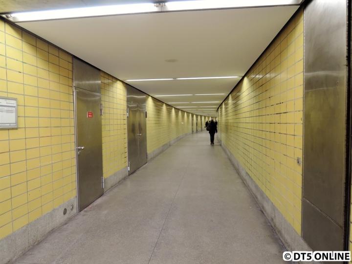 Dem Eingang schließt sich ein Verbindungsgang an, links und rechts vom Tunnel fährt die U2.