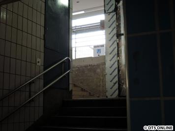 """Blick am zur Zeit geschlossenen Aufgang hinauf. Hinten steht """"U Eingang"""" mit einem Pfeil, nur ist dieser Hinweis, wo der EIngang denn sei, nicht fahrgastfreundlich außen angebracht, sondern innen... Hat jemand wohl mal den Bauzaun gedreht."""