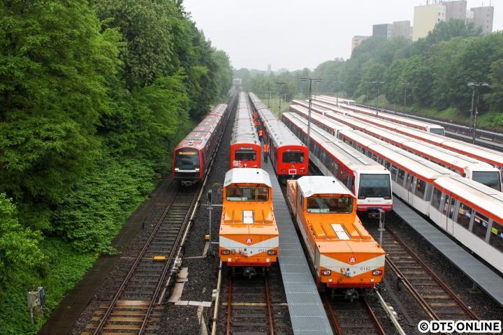 """Am 26. Mai rückte das erste Vollstrecker-Kommando der Hochbahn an – der Abtransport der letzten vierzehn DT2-Einheiten nach Lübeck sollte beginnen. Eines der letzten Male passiert ein DT5-Verband die geschlossene DT2-Schrottreihen. Während die Aktion beim ersten Mal noch etwas dauern sollte, erreichte man dann doch nach und nach eine Routine beim Abtransport. Eine Akkulok """"holte"""" sich immer zwei Einheiten (zuerst auf dem hier linken Gleis), die zweite Akkulok wurde in der gegenüberliegenden Kehre Ost angekuppelt."""