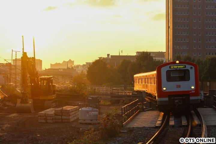 Zum Abschluss dieses Jahres noch einmal ein Foto aus der goldenen Stunde: 472 001 erreicht als S2 den Bahnhof Berliner Tor. Im vollen Gegenlicht erkennt man im Hintergrund Hamburgs neues Wahrzeichen, die Elbphilharmonie, während der Bagger vorn ganz von den Bauarbeiten an diesem Bahnknoten zeugt. Während jetzt bei der Fern- und Regionalbahn fleißig gebaut wird, wird auch die S-Bahn-Station gegen Ende des Jahrzehnts dran sein. Ab 2018 ist die Erneuerung der S21-Brücken vorgesehen, danach die Sanierung der Station.