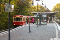 Quer über den Bahnsteig mit Stationsschild und Bahnhofsgebäude...