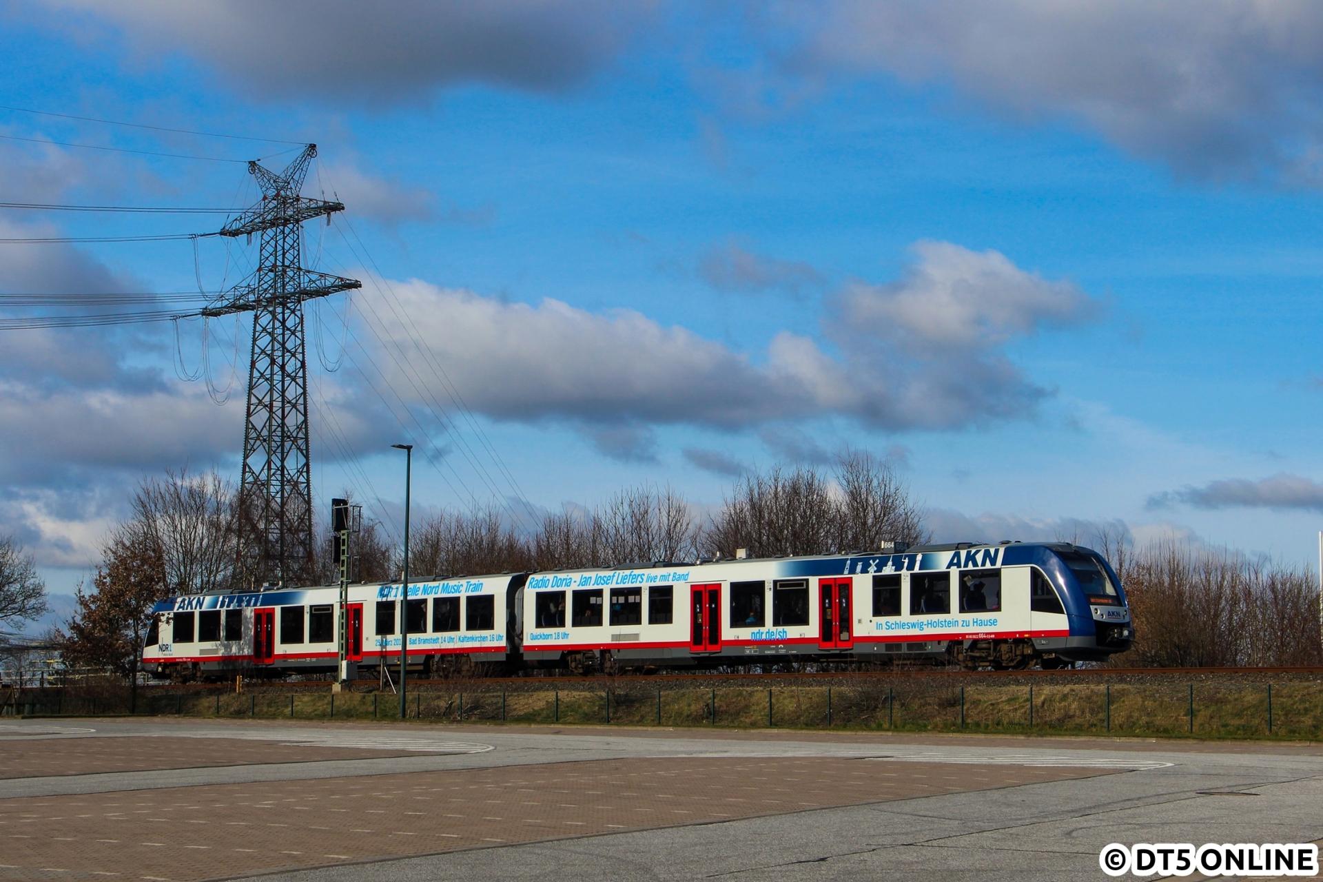 """Am 25. März war Jan-Josef Liefers mit seiner Band """"Radio Doria"""" im NDR1 Welle Nord-Music Train unterwegs. Hier konnte der entsprechend beklebte AKN-Zug über den leeren Parkplatz von dodenhof fotografiert werden."""