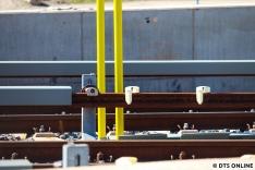 Diese kleine Detailaufnahme zeigt, wie die Stromschienen bei der U-Bahn aufgehängt werden. Direkt daneben stehen auch die Schutzhalt-Signale. Auch die Ausfahrtssignale sind bereits aufgestellt, auf ihnen ist das Kürzel EB bereits zu lesen.