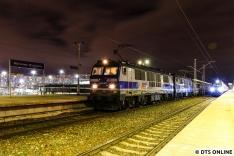 Eine EP09-Lok samt Intercity mit dem Stationsschild.